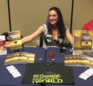 "Kitty Chambliss with her ""Jealousy Survival Guide"" book display complete with a free LWB condom and wristband giveaway, and the ""Be The Change"" t-shirt."